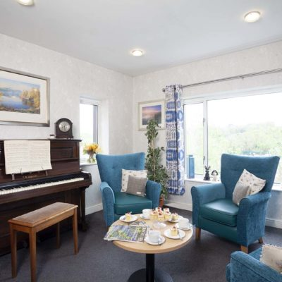 Turquoise chairs and piano in living room at chestnut view care home haselmere